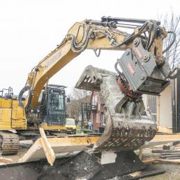 """De første spadestik blev taget, da der var """"Bulldozer Dag"""" i anledning af opførelsen af den nye arkitektskole ved Godsbanen i Århus. Her en entreprenørrmaskine godt i gang med at rive en bygning ned for at gøre plads til Arkitektskolens nye hus."""